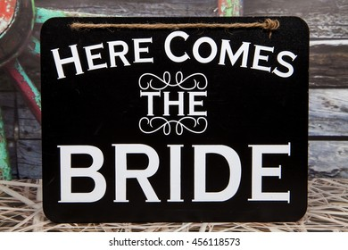 A here comes the bride sign against a rustic background