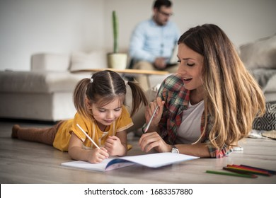 I'm here to help you. Family at home. Mother helping her daughter with homework. Focus on foreground.