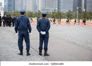 Here in the image two on duty Japanese police officers standing and watching people to maintain law and order in the area. And few people can be seen standing in a queue in the picture.