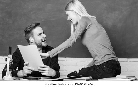 Here is information we need. Pretty teacher and handsome schoolmaster grading papers. High school education. University or college students. Man and woman back to school. Couple studying in classroom.
