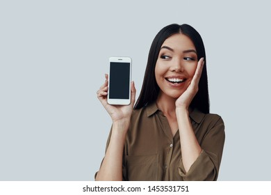 Here it is! Attractive young Asian woman showing smart phone and smiling while standing against grey background