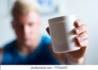 Here it is. Selective focus of a jar with bodybuilding supplement in hands of a strong man holding it
