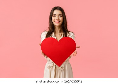 Here my love to you. Charming tender and alluring, romantic young woman giving big heart card to camera, smiling delighted, express her affection and admiration, standing pink background