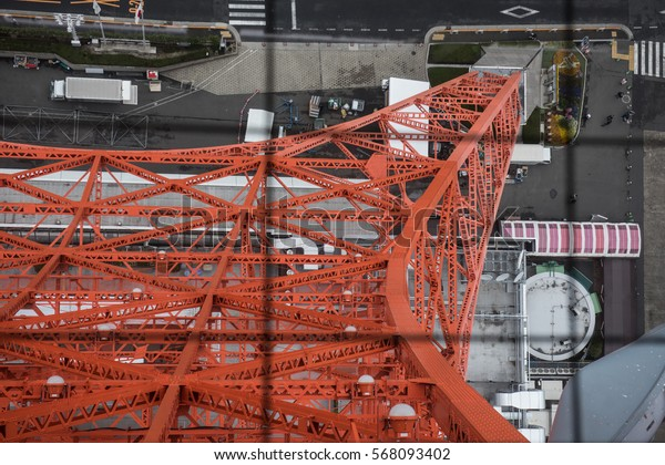 Here in the picture we can see this red colored network tower from a different angel. Few vehicles and people can also be seen in the picture.