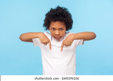 Here and right now! Portrait of angry capricious little boy with curls pointing down, gesturing below with strict aggressive expression, unruly child demanding to fulfill whim now. indoor studio shot