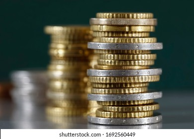 Here are three piles of coins which have been stacked on a grey, flat surface and against a dark green background.