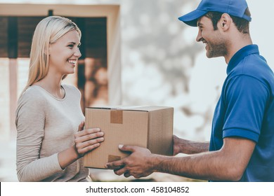 Here you go! Side view of happy young delivery man giving a cardboard box to young woman while standing in front of the house