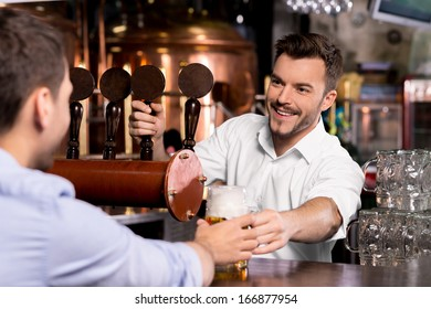 Here is your beer. Cheerful young bartender giving a mug with beer to the customer