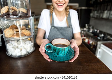 Here is your order. Focus on close up hands of cheerful female giving cup of delicious coffee to client