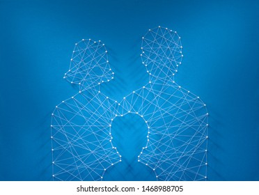 Heritage concept. Network of pins and threads in the shape of a father, a mother and a child symbolising the depth of family connections.