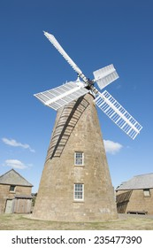 Heritage listed museum building of historic flour windmill with white wings at Oatlands, Tasmania, Australia, built in the 19th century, mill restored and still working, blue sky and copy space.