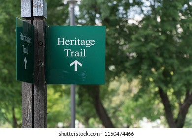 Heritage Trail sign on wood post marking symbol for nature hike walk through historical landmarks
