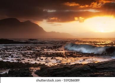 Hermanus, South Africa - Large waves wash kelp ashore at sunset in Western Cape