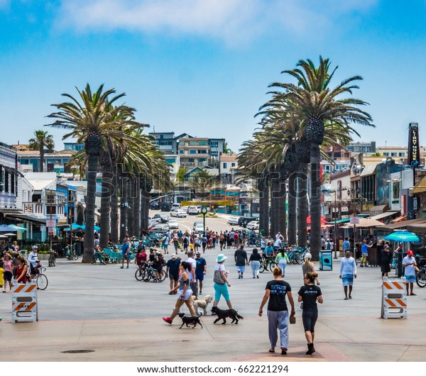 Hermosa Beach, California - June 18, 2017: People enjoy the day at the Hermosa Beach Pier Plaza, including dog walkers and bicyclers on a warm summer day.