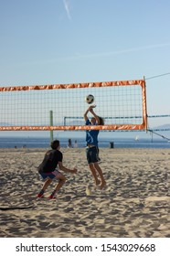 Hermosa Beach, California / United States of America - October 26 2019: A young boy about to set a volley ball over the net in a game against his friend on Hermosa Beach.