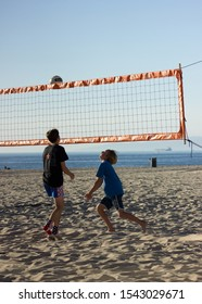 Hermosa Beach, California / United States of America - October 26 2019: Two young boys playing volleyball on hermosa beach