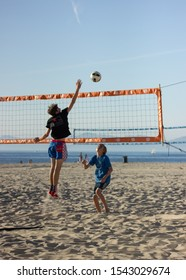 Hermosa Beach, California / United States of America - October 26 2019: Two young boys playing a game of volley ball on Hermosa Beach. Boy is about to spike.
