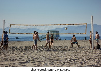 Hermosa Beach, California / United States of America - October 26 2019: A group of men playing a game of volleyball on Hermosa Beach