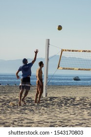 Hermosa Beach, California / United States of America - October 26 2019: A player serving the ball in a casual volleyball game on Hermosa Beach