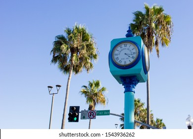 Hermosa Beach, California / United States of America - October 26 2019: A blue clock tower at Hermosa Beach, California towering over Pier Avenue, surrounded by palm trees.