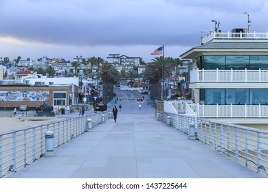 HERMOSA BEACH, USA - MAY 21, 2019: Entrance of the Hermosa Beach Pier (Los Angeles) in the morning. A few people strolling around the walkway.