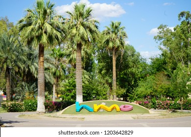 """Hermosillo, Sonora / Mexico - 6-29-2018: Located in the center of the city or """"El Centro,"""" is the park """"Parque Madero"""". Palm trees hover over the letters HMO that are an abbreviation for Hermosillo."""