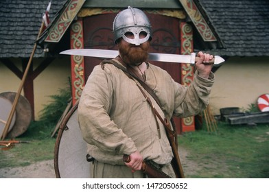 Herne Kent UK June 2019 Mike of Regia Angolorum in front of a Long House he wears the period clothing of an 11th Century Huscarl he wears a spectacle helmet, sword in hand at a living history event.