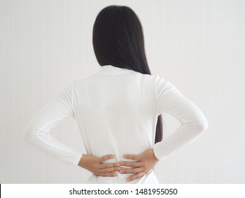 herniated disc,spondylosis and scoliosis in asian woman and she touching her back symptom of low back pain cause of cause of strains or disc injury and spinal stenosis use for health care concept.