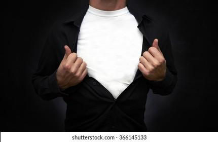 Hero pulling open black shirt showing white t-shirt on blackboard background