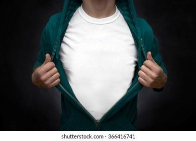Hero pulling open turquoise blouse showing white t-shirt on blackboard background
