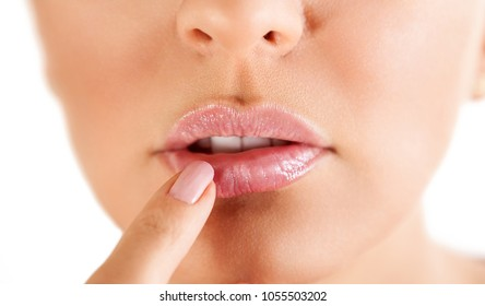 herpes on the lips, part of a woman's face with finger on lips with herpes, beauty concept