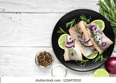 herring fillet with pepper, rosemary, onion and lemon on black plate on white background. top view with copy space. healthy food