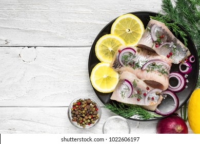 Herring fillet with salt, pepper, herbs, onion and lemon on black plate with ingredients on white background. top view. healthy food