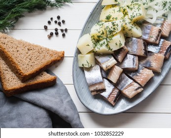 Herring fish with potatoes slices and red onion, rye bread on the white table. Top view