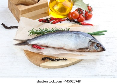 Herring with onion and rosemary on the wood background