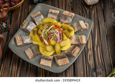 herring, pickled cucumber, beet, potato and eggs salad on white plate, top view