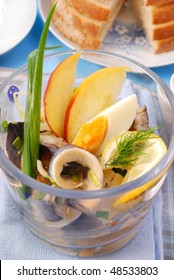 herring salad with egg and apple in glass bowl