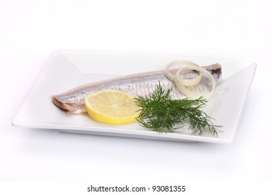 herring salt fillet with onion and lemon on white dish
