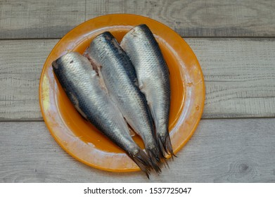 Herring with salt, pepper, herbs and lemon on white ceramic plate on white background. Herring lies in a plate on a wooden light background. Sea fish. Food photography. Tasty salted fish. Fish food