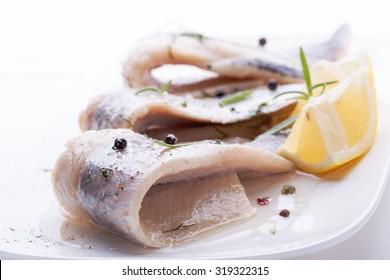 Herring with salt, pepper, herbs and lemon on white ceramic plate on white background