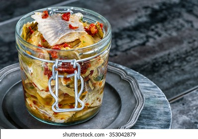 Herring with salt, pepper, herbs, onion, dried tomatoes and lemon on  plate on grey background. Marinated herring in a jar with vegetables and herbs