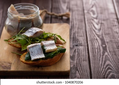 Herring sandwich (traditional Danish smorrebrod) on cutting board. Copyspace.
