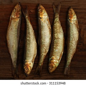 herring sprat fish smoked on  wooden table background
