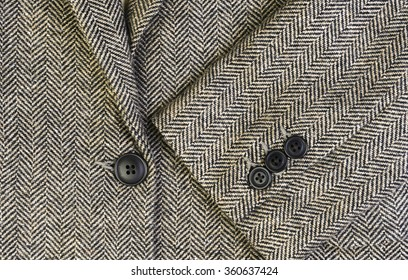 Herringbone tweed women jacket with closeup on wool fabric texture with buttons