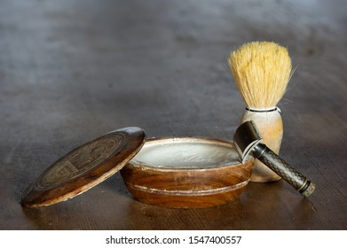 Herrnhut, Saxony/Germany - November 1st 2019: wooden bowl of crabtree & evelyn shaving soap with razor and shaving brush on wooden table surface with copy space