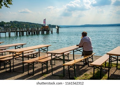 Herrsching,Germany-August 20,2018: A man sits by himself in a biergarten looking out to the waters of lake Ammersee
