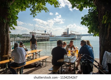 Hersching,Germany-July 14,2018:People sit in a biergarten by the shore of Lake Ammersee as paddle boat leaves  the dock.