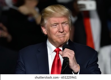 "HERSHEY, PA - DECEMBER 15, 2016: President Donald Trump grabs the microphone before delivering a speech at the Giant Center. It was billed as the ""Thank You"" tour."