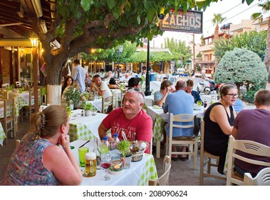 HERSONISSOS, GREECE - JULY 22, 2014: Creten Dinner Time - People eating dinner outdoors in Greek Tavernas at Hersonissos Old City Square in Crete, Greece