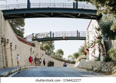 Hersonissos,Crete/Greece - 07.03.2018: Couple of resort bridges in Hersonissos, Greece. Tourists walking next to a stone wall.